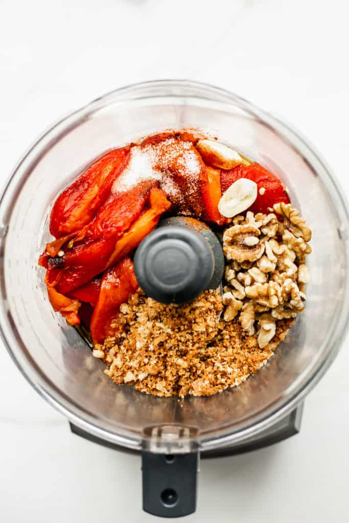 a food processor with red peppers, breadcrumbs, walnuts and garlic in it