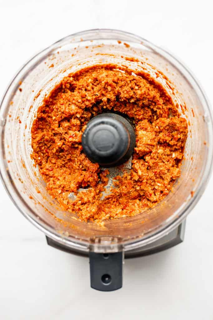 a food processor with roasted red pepper dip in it