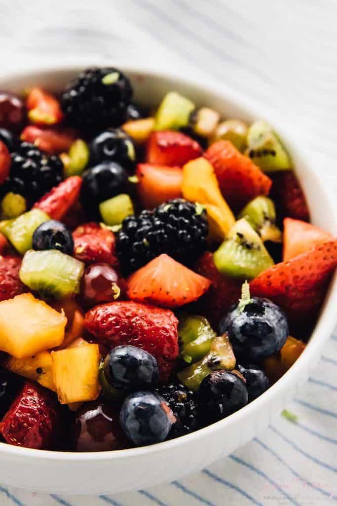 white bowl of fruity summer salads of blackberries, strawberries, kiwi, and mango against a white and blue striped linen