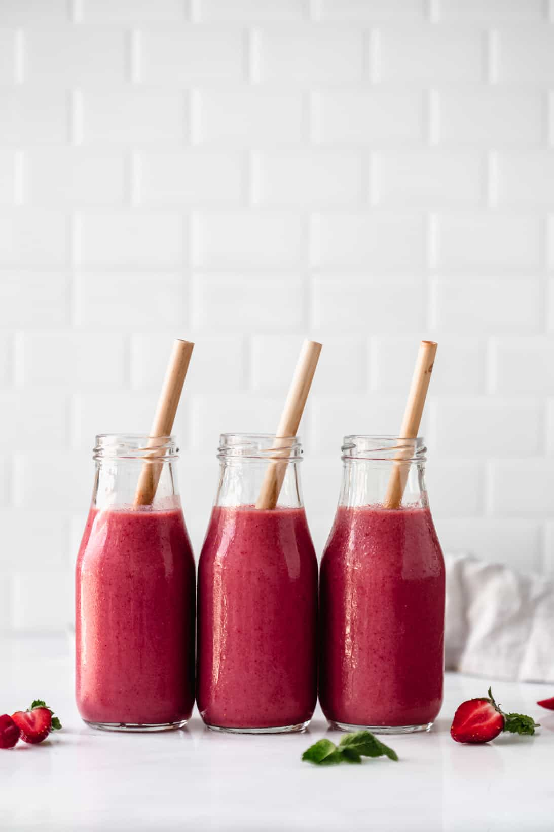 three bottles of berry smoothie with bamboo straws in them