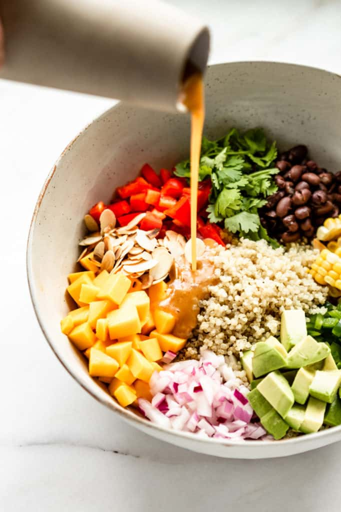 Salad dressing being poured into a bowl of quinoa salad