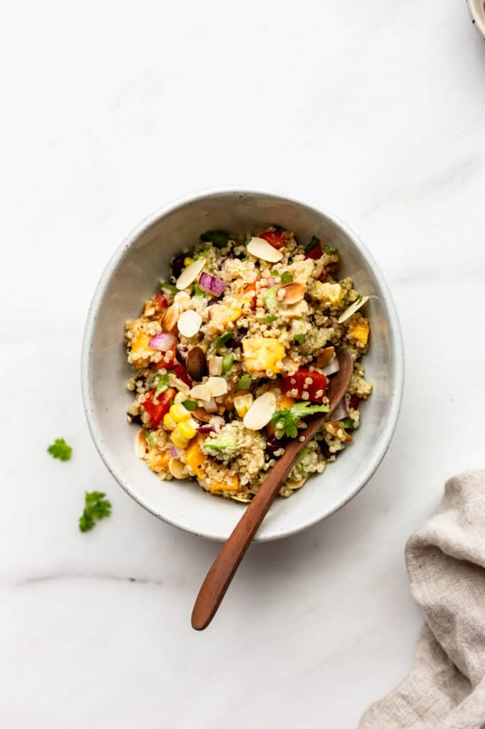 A bowl of southwest quinoa salad with a linen napkin on the side