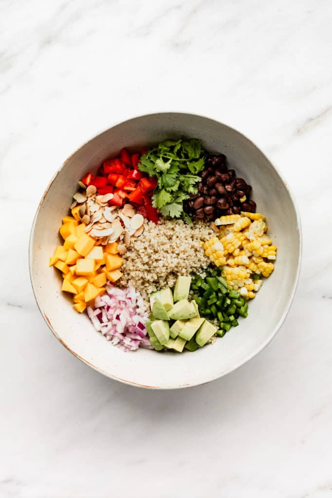 A large mixing bowl with quinoa, black beans, corn, avocado, jalapeno, red onions, mango, almonds, red pepper and cilantro in it