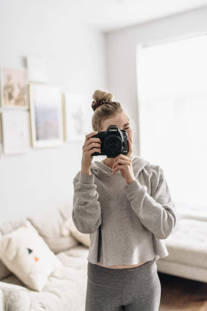 girl holding a canon camera taking a photo