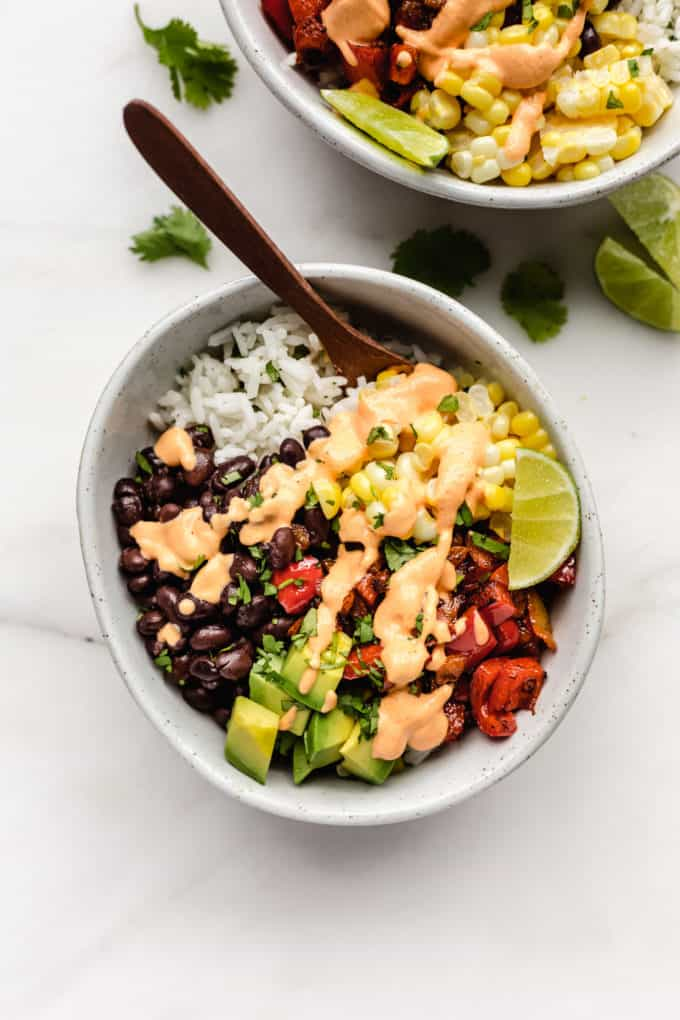 A vegan burrito bowl topped with chipotle crema in a bowl with a wood spoon