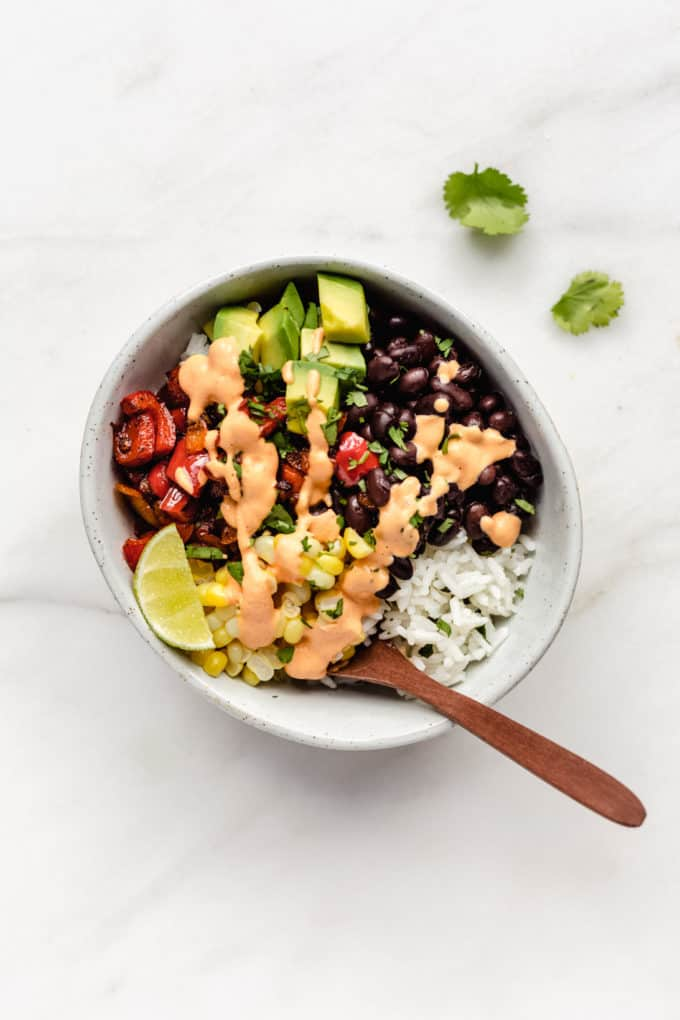 A vegan burrito bowl with rice, beans, corn, peppers and avocado in a white bowl