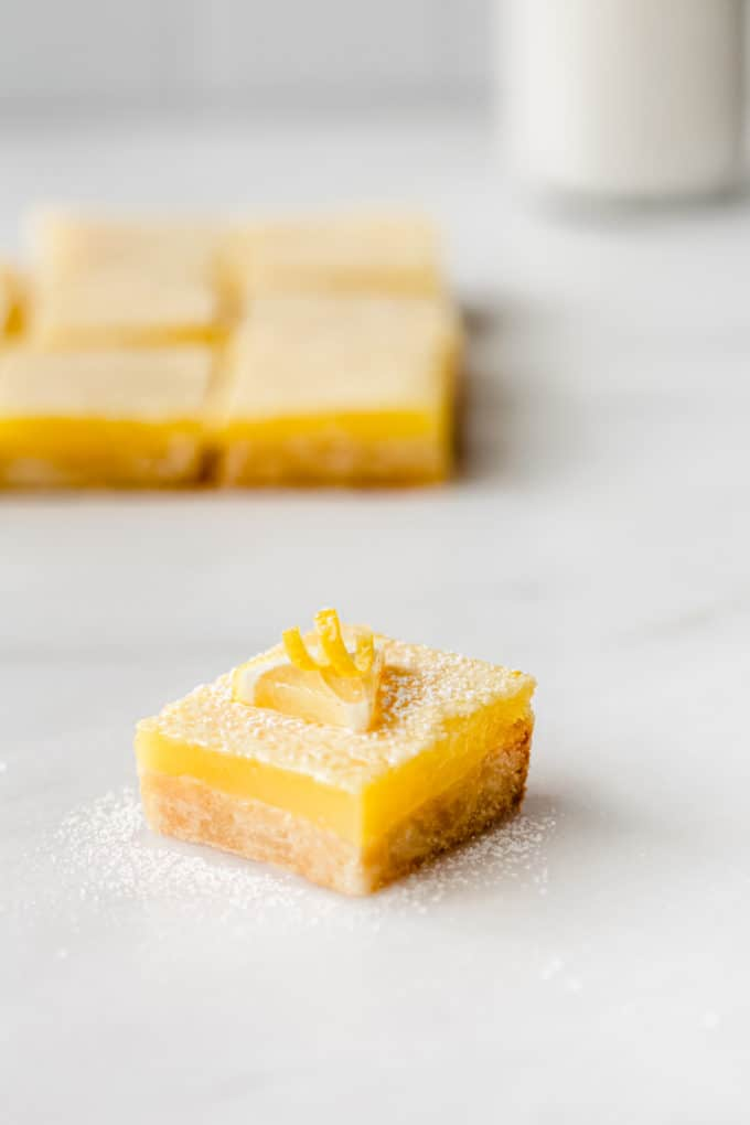 a lemon square topped with a slice of lemon on a marble board