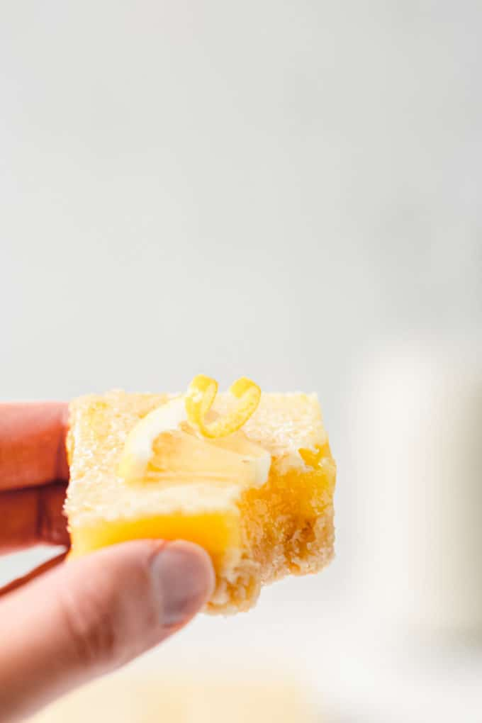 a hand holding a lemon bar