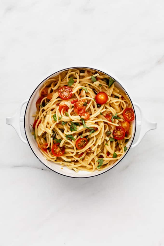 a white pot filled with linguine pasta, cherry tomatoes, capers and basil
