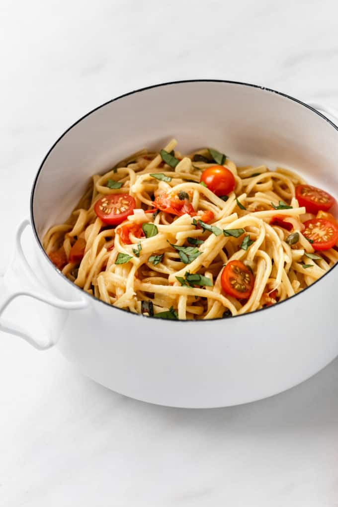 linguine with basil and cherry tomatoes in a white pot