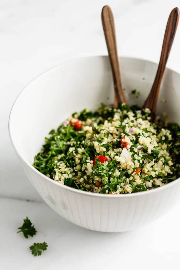 white mixing bowl filled with tabbouleh salad made with quinoa with two wooden spoons sticking out of the bowl
