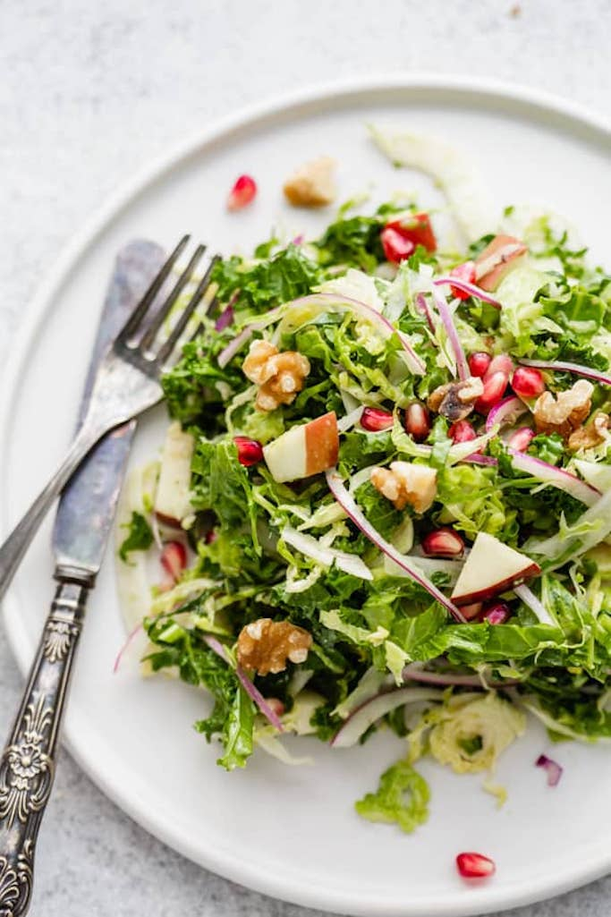 summer salads made with shaved brussels sprouts, kale, fennel, and chopped apples topped with walnuts and pomegranate seeds on a glossy white plate with a silver fork and knife