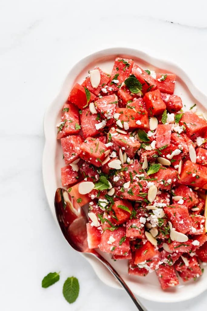cubed watermelon with slivered almonds, feta cheese, and chopped mint leaves on a white serving platter on a white marble countertop, summer salads with watermelon
