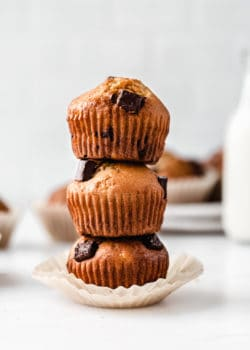 thee banana muffins with chocolate chunks stacked on top of each other