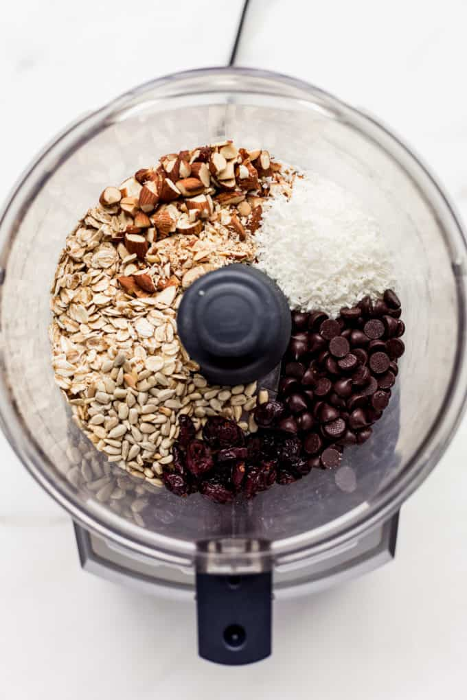a food processor with nuts, seeds, shredded coconut and chocolate chips in it