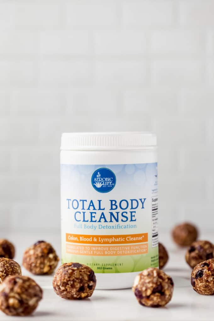 a jar of nutritional brand total body cleanse with energy balls around it