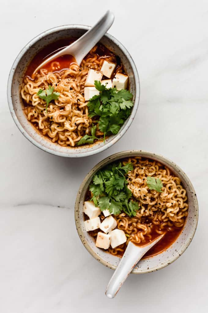 two white speckeld ceramic bowls of kimchi ramen with spoons in them