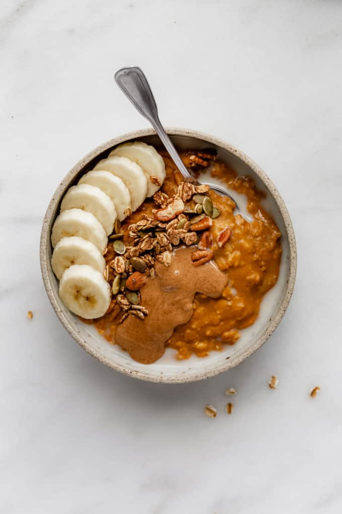 pumpkin pie oatmeal in a bowl topped with bananas, granola and almond butter
