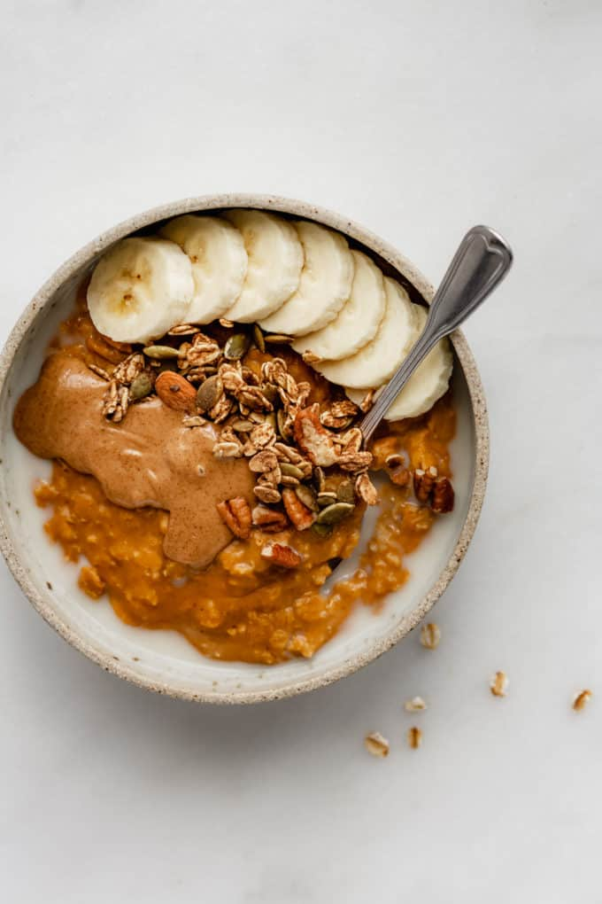 pumpkin oatmeal in a bowl topped with bananas and granola
