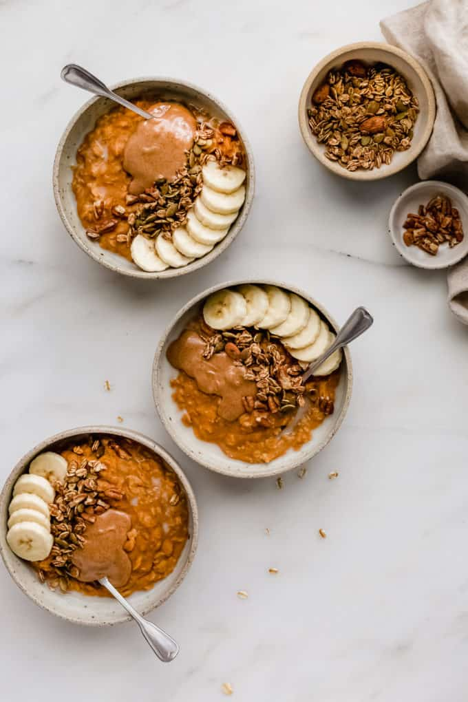 three bowls of pumpkin pie oatmeal with small bowls of granola and pecans on the side