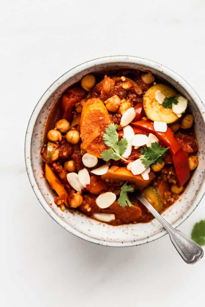 A bowl filled with vegetable tagine topped with almonds and cilantro