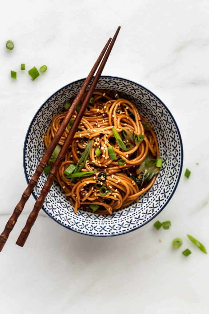 a bowl of teriyaki noodles with chopsticks on top
