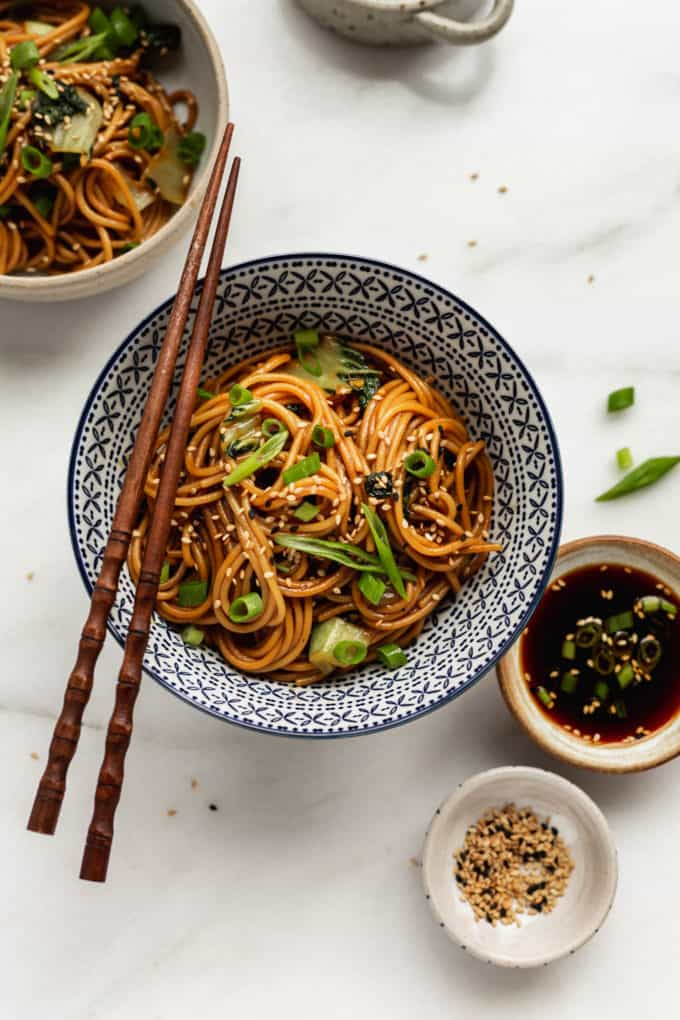 Teriyaki noodles in a blue bowl with a side of teriyaki sauce and sesame seeds