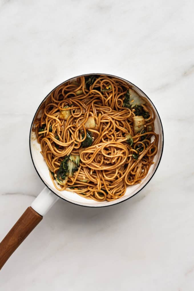 teriyaki noodles with bok choy in a white pot with a wood handle