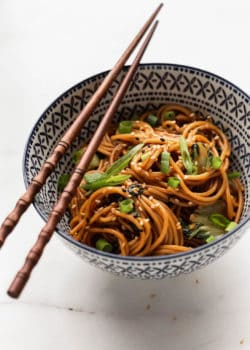 a bowl of noodles topped with green onions and sesame seeds
