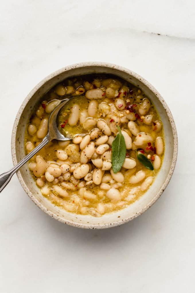 A bowl of cannellini beans in broth with a spoon
