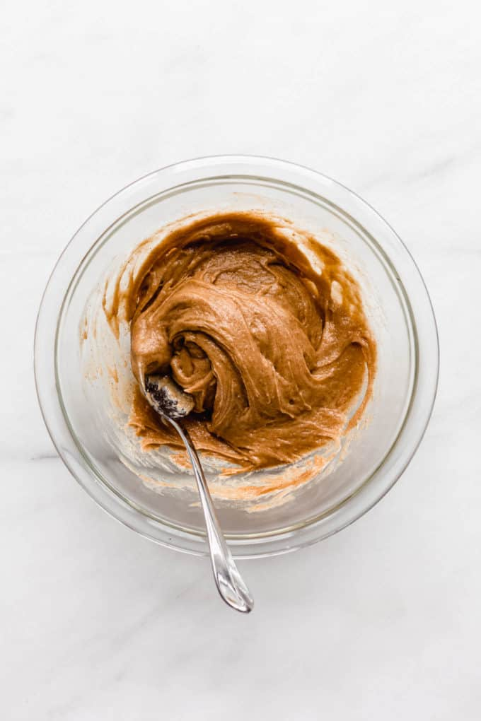 almond butter in a clear mixing bowl with a spoon