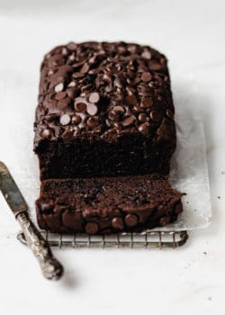 A loaf of healthy chocolate pumpkin bread topped with chocolate chips with a small knife on the side