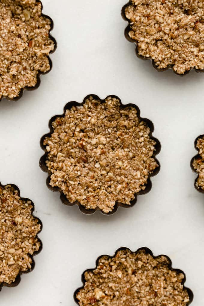 mini tart pans with pecan crust in them
