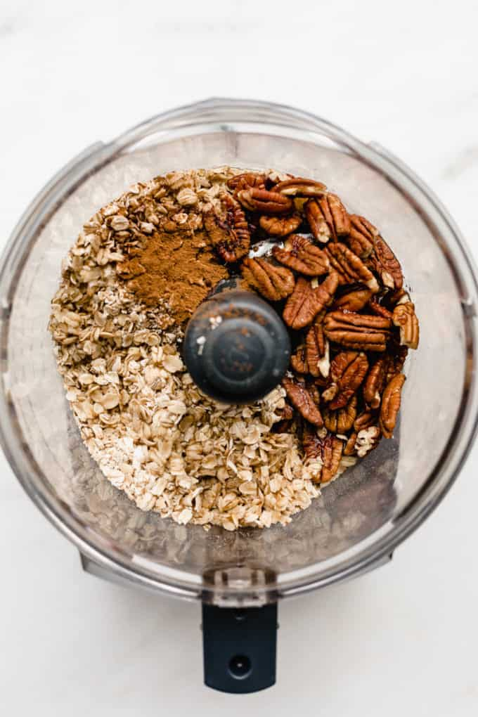 A food processor with oats, pecans and cinnamon in it