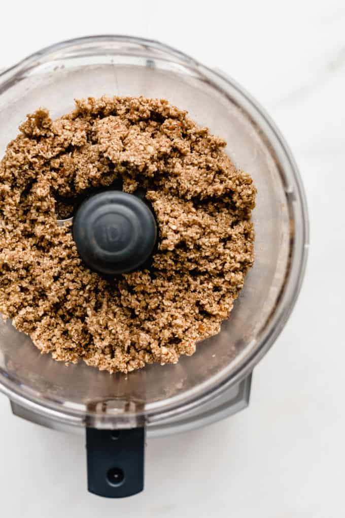 a food processor with blended pecan pie crust in it