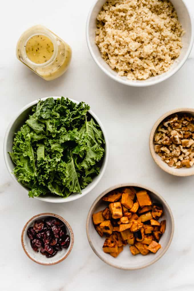 Kale, quinoa, sweet potato, walnuts, cranberries and salad dressing in bowls on a marble baord