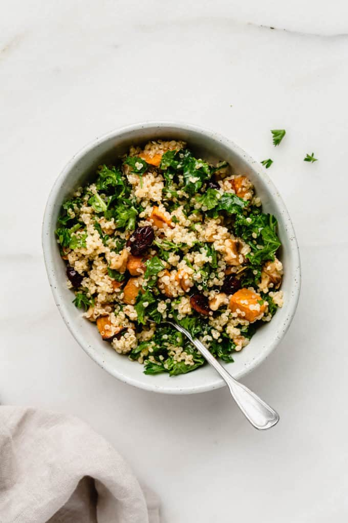 A bowl of quinoa kale salad with sweet potatoes in a white bowl with a napkin on the side
