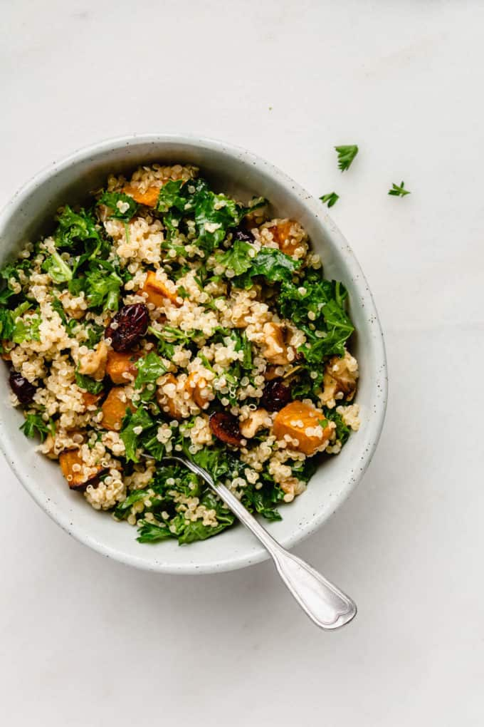 Quinoa and kale salad with sweet potatoes and cranberries in a bowl with a spoon