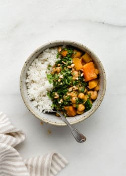 A bowl filled with white rice and pumpkin chickpea curry topped with cilantro and peanuts