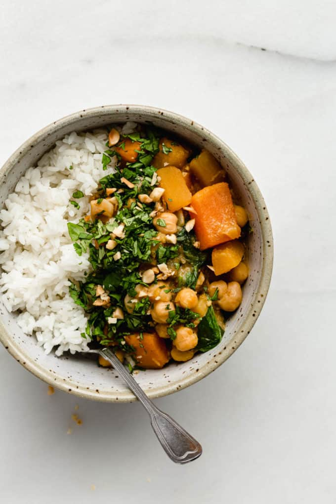 A bowl of pumpkin chickpea curry and rice with a spoon in it