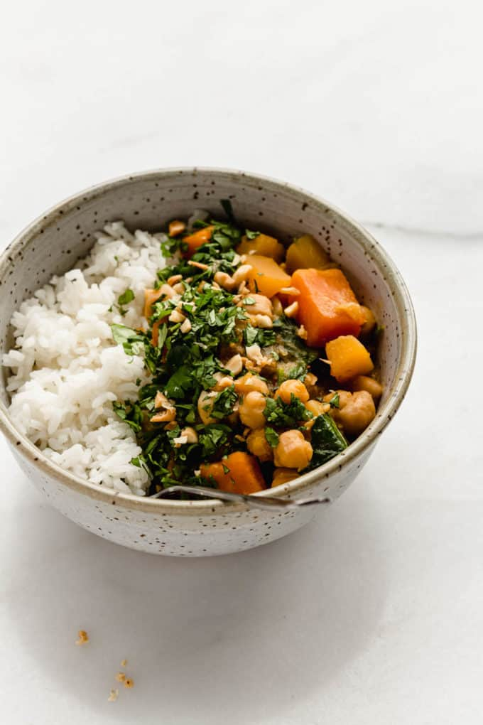 A speckled light blue bowl with rice, chickpeas and pumpkin curry in it