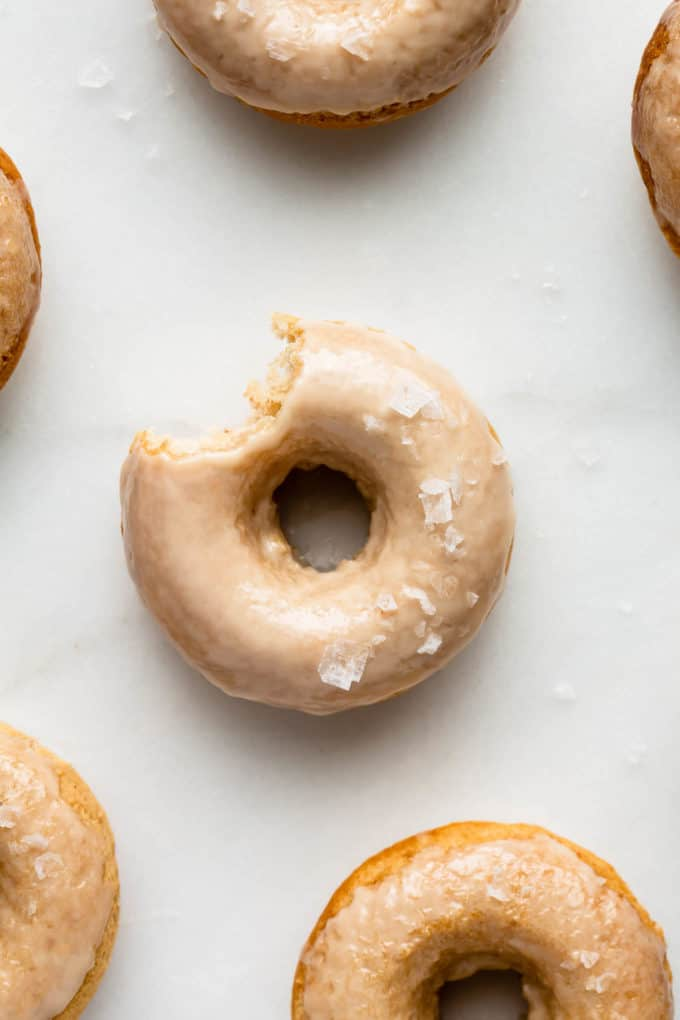 Maple donuts on a marble board topped with sea salt