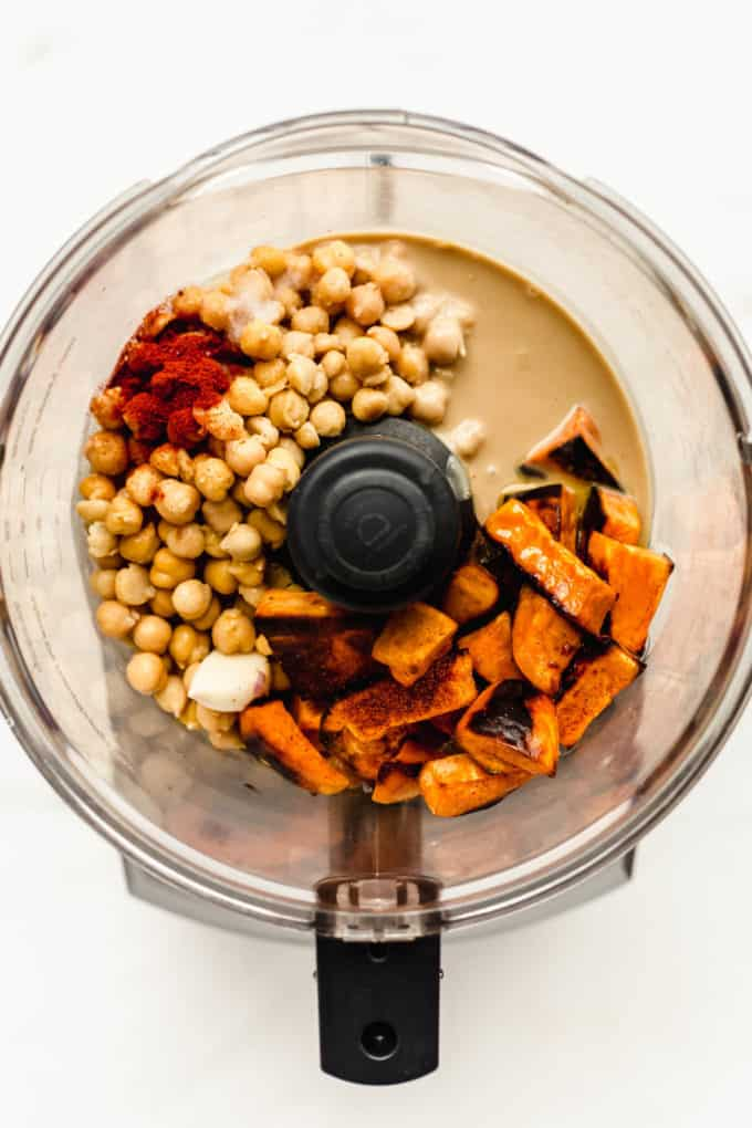 a food processor with sweet potato, tahini, chickpeas, garlic and paprika in it