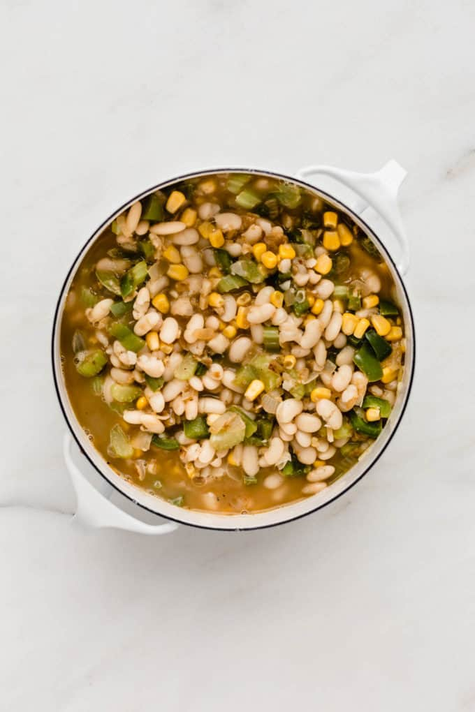 A white pot with broth, white beans, green peppers and corn in it
