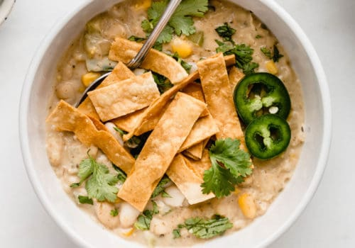 A white bowl with white vegan chili in it topped with tortilla strips and cilantro