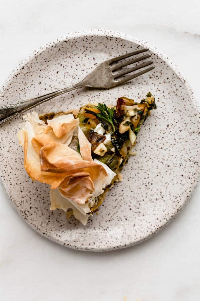 A slice of veggie skillet phyllo pie on a white speckled plate with a fork on the side.