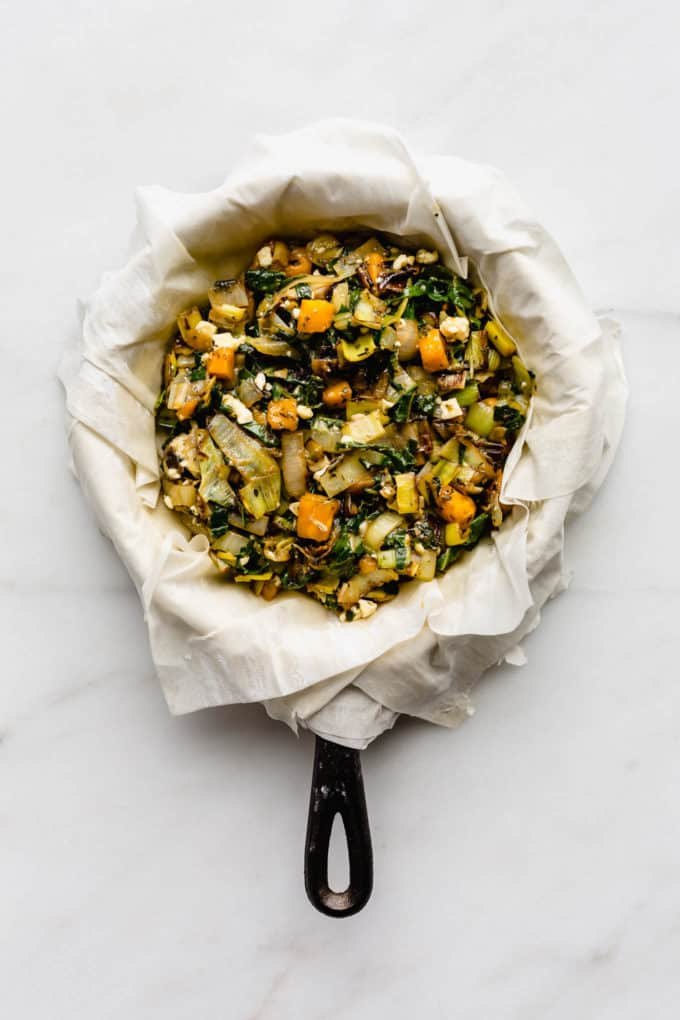 phyllo dough draped over a cast iron skillet filled with sauteed veggies