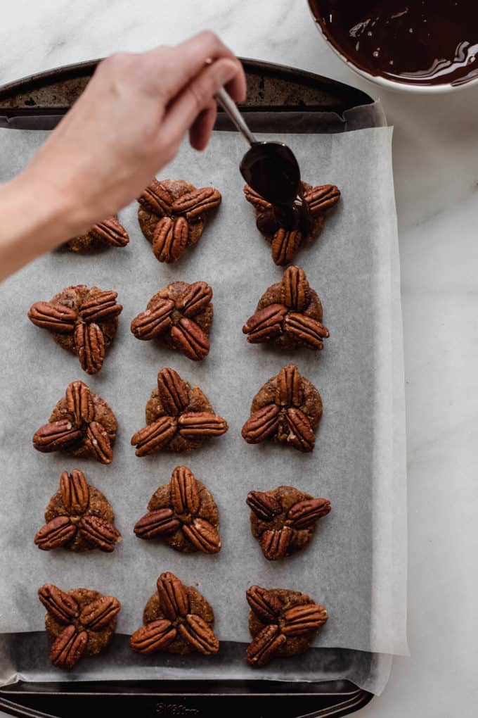 A hand drizzling melted chocolate onto a tray of date and pecan candies