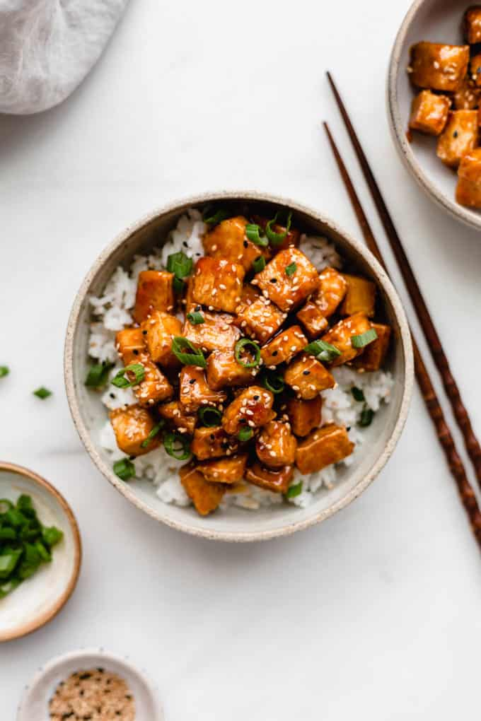 Sweet and sour tofu in a white ceramic bowl with two small bowls on the side filled with green onions and sesame seeds