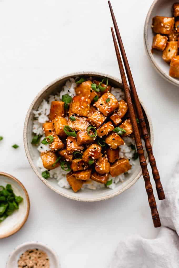 A bowl of sweet and sour tofu on a marble counter with wooden chopsticks